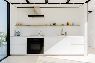 The kitchen is equipped with Sub-Zero and Wolf appliances, and the cabinet faces and handles match the built-ins in the other rooms.
