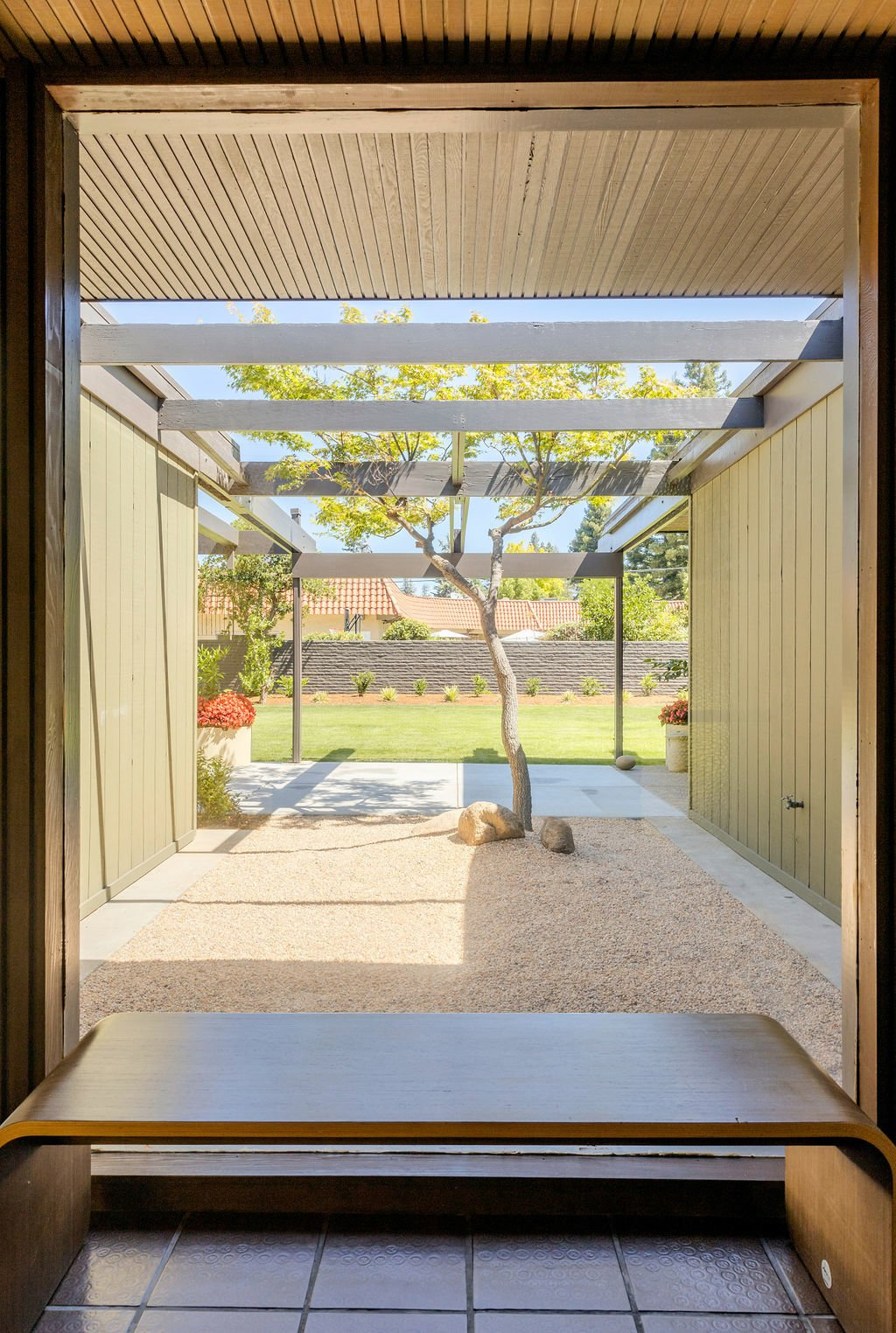 Floor-to-ceiling windows in the entryway provide views of the centrally placed Japanese Maple.  Photo 9 of 16 in A Restored Post-and-Beam by a Richard Neutra Protégé Lists for $700K