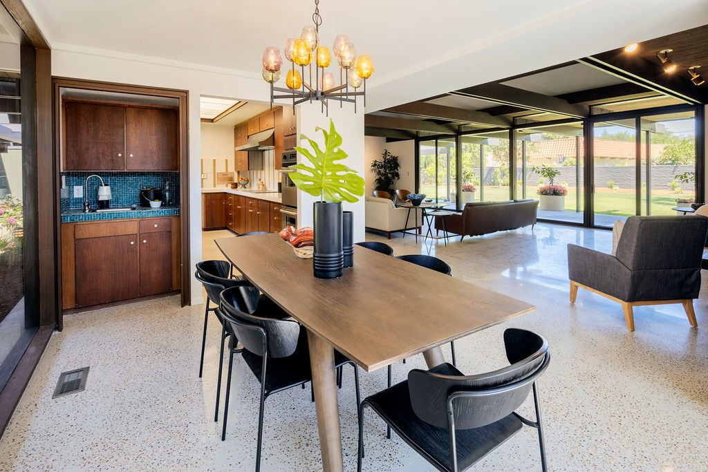 The dining area features an original glass chandelier, as well as a corner bar with Venetian tile and more built-in Nutone appliances.  Photo 7 of 16 in A Restored Post-and-Beam by a Richard Neutra Protégé Lists for $700K