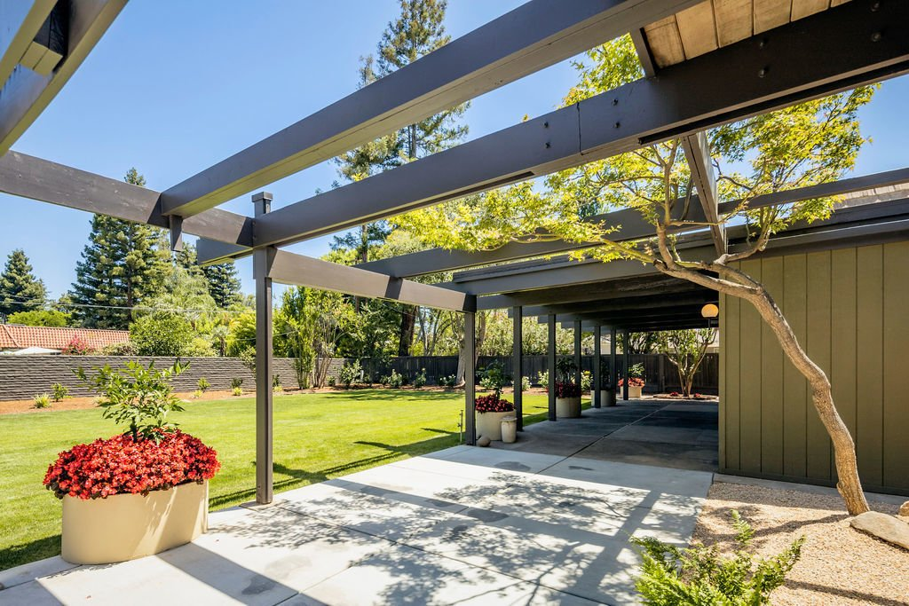 Outside, the post-and-beam construction extends out over the partially covered patio.  Photo 13 of 16 in A Restored Post-and-Beam by a Richard Neutra Protégé Lists for $700K