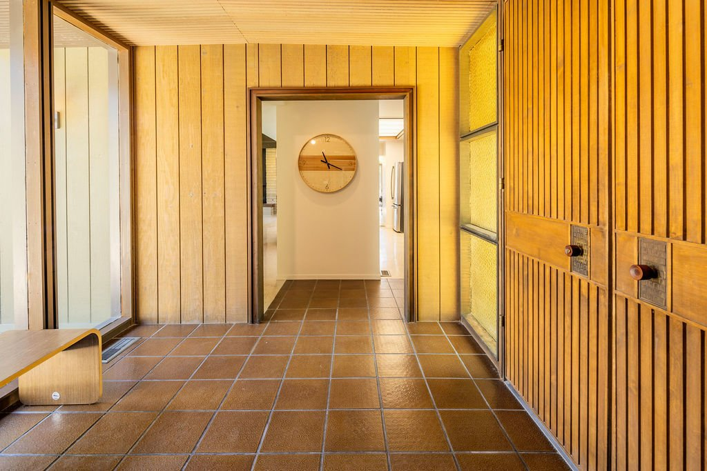 In the entryway, patterned amber-colored glass flanks both sides of the double walnut door.   Photo 8 of 16 in A Restored Post-and-Beam by a Richard Neutra Protégé Lists for $700K