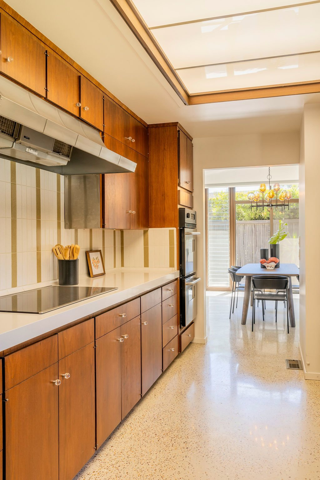 An opposite view of the kitchen looking toward the dining area.  Photo 6 of 16 in A Restored Post-and-Beam by a Richard Neutra Protégé Lists for $700K