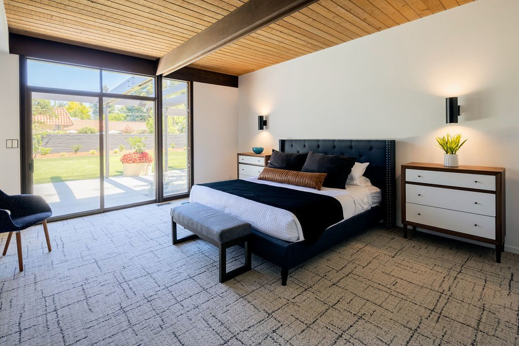 In the private wing of the home, the master bedroom features sliding glass doors that lead to the backyard.  Photo 10 of 16 in A Restored Post-and-Beam by a Richard Neutra Protégé Lists for $700K