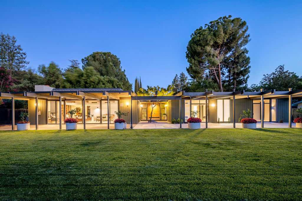 Floor-to-ceiling windows allow the interior to glow at night, highlighting the home's architectural features and landscaping.  Photo 15 of 16 in A Restored Post-and-Beam by a Richard Neutra Protégé Lists for $700K
