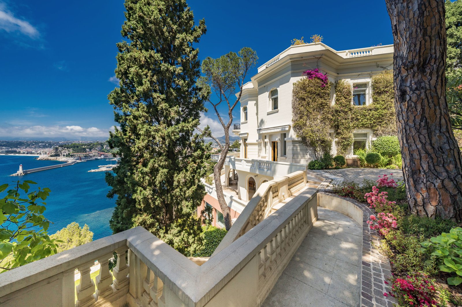 """Outdoor, Side Yard, Trees, Shrubs, Flowers, and Large Patio, Porch, Deck Positioned in a prime location, the estate—which is still referred to locally as """"Sean Connery's home""""—is perched above Port de Nice and sits just 30 minutes from Monaco.  Photo 9 of 11 in Scottish Actor Sean Connery's Former Seaside Villa Looks Like the Perfect Place to Quarantine"""