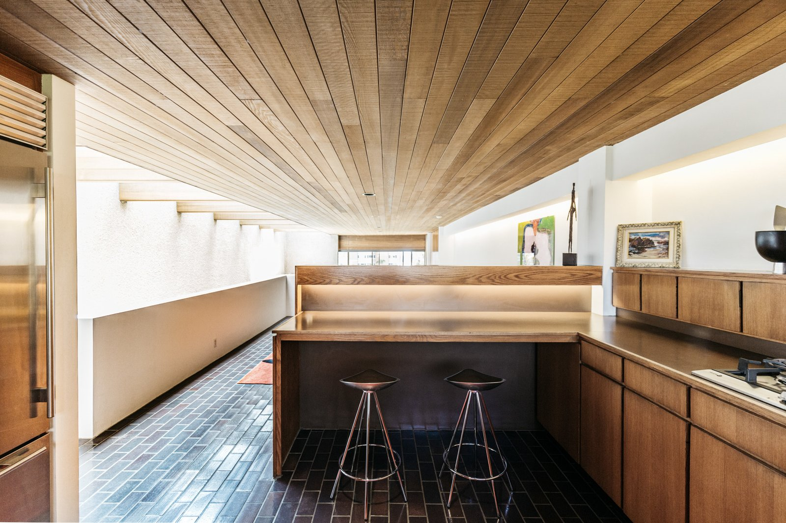 The kitchen sits at the rear of the top level—accessible from the central staircase, as well as a second staircase in the corner of the home. White oak cabinetry and Argentine granite wrap around the space.  Photo 8 of 15 in A Luminous L.A. Beach House With All-Original Features Asks $2.3M