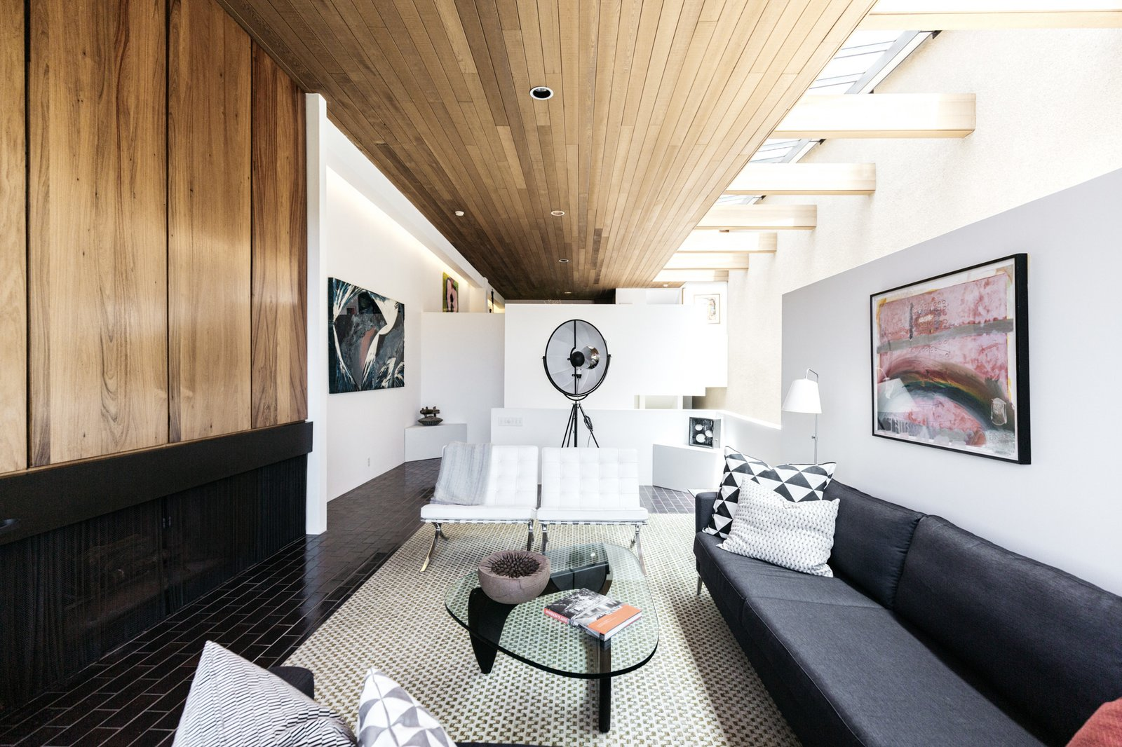 Another view shows the continuously running clear heart redwood ceiling that tops the living room and upper-level dining area and kitchen in the back.  Photo 5 of 15 in A Luminous L.A. Beach House With All-Original Features Asks $2.3M