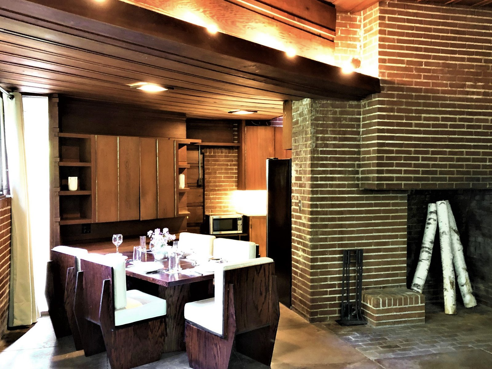 A dining nook opposite the fireplace features furniture that the current owners had built in accordance with Wright's original designs for the home. An original cabinet in the back features full-length piano hinges along each door.  Photo 5 of 10 in One of Frank Lloyd Wright's First Usonian Houses Hits the Market in Wisconsin for $425K