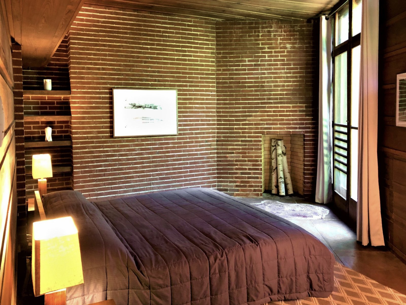 On the opposite side the house are four bedrooms and three bathrooms. In the master bedroom (shown here), the current owners restored the fireplace, added shelving, and removed windows all to realign the design with Wright's original plans.  Photo 7 of 10 in One of Frank Lloyd Wright's First Usonian Houses Hits the Market in Wisconsin for $425K