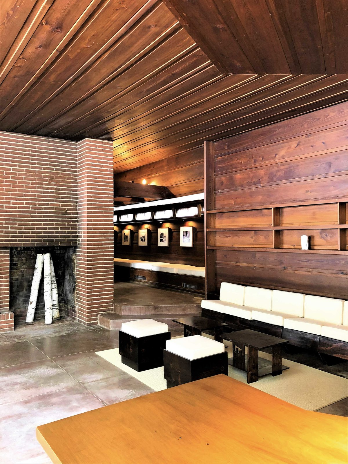 Another view of the living area shows the floor-to-ceiling fireplace. Local Ringle bricks and red tidewater cypress are used throughout the interior, aligning with the exterior facade.  Photo 2 of 10 in One of Frank Lloyd Wright's First Usonian Houses Hits the Market in Wisconsin for $425K