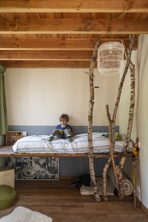 Nine-year-old Stan reads on the platform bed his father built for him. A trio of birch branches helps to bring the outdoors in. The pendant and bed linens are custom.