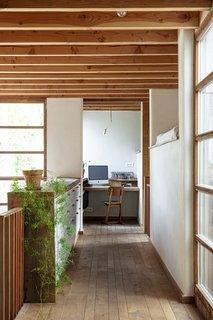 在增加了窗帘,走廊上方的利基将成为一个客人的睡眠区。这把椅子是从宜家。