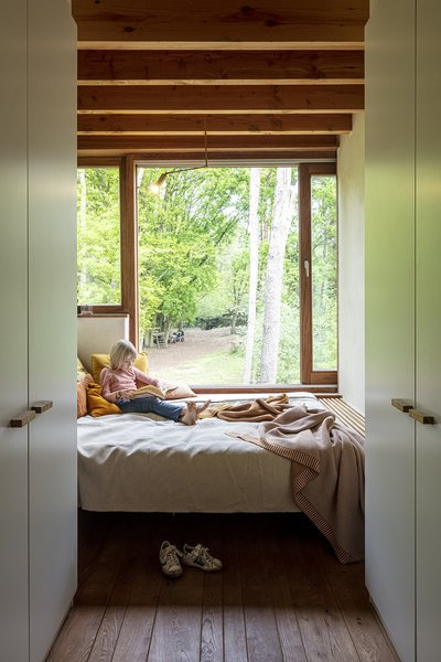 The master bedroom features a closet in the corridor to use less space. Sight lines lead to the forest from nearly every space.