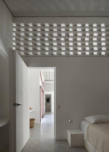 Natural light permeates the brickwork to illuminate a bedroom.
