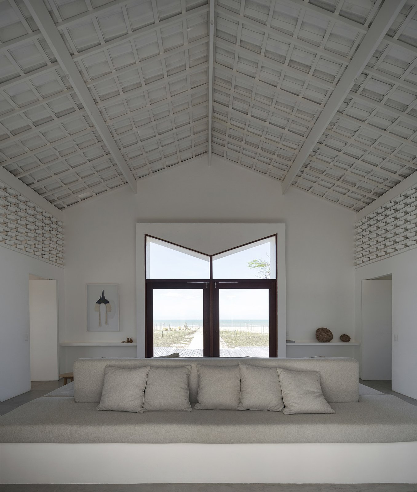 In the living room, open brickwork along each side allows light and air to permeate the home.  Photo 7 of 16 in A Stark White Residence Signals the Renaissance of a Brazilian Fishing Town