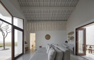 The airy feeling is accentuated by painted white walls and white ceramic roof tiles that are visible on the ceiling. The tile motif was adapted from Portuguese colonial architecture and remains prominent in the region. The custom two-sided sofa is by Atelier Branco.