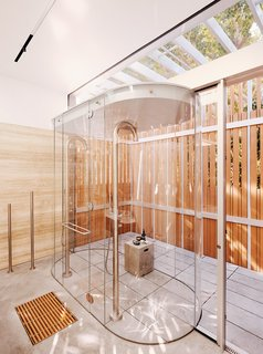 A double-sided, free-standing vanity and a shower wrapped in a glass lozenge create an indoor/outdoor experience at a San Francisco residence designed by Fougeron Architecture.