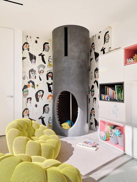 The playroom is outfitted with Bubble armchairs by Sacha Lakic from Roche Bobois and a custom fire pole that descends from the floor above. The wallpaper is FP502001 Shaman from Pierre Frey.