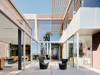 "The redesigned rear facade wraps around a central courtyard. ""We had to keep the overall shape of the house,"" says Fougeron, referring to the city's stringent building codes, ""so we started to weave the design into the existing conditions."" The chairs are from B&B Italia."