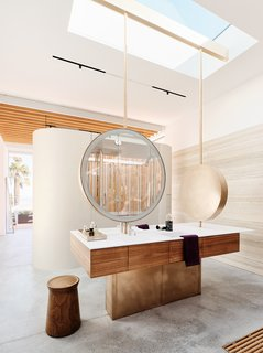 "Circular mirrors by Dennis Luedeman join a custom walnut vanity with a counter and integrated sink by Corian. ""The house is relentlessly linear, but we were able to add these more playful shapes,"" Fougeron says. The faucets are V1/150 by Vola."