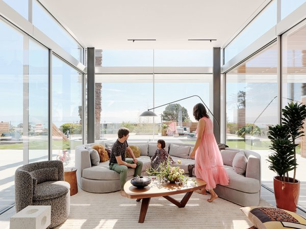 Homeowners Ligaya Tichy and Russel Simmons relax with their daughter, Skye, in the family room, which occupies a new glass pavilion. A custom rug by Vaheed Taheri snugly fits into the space, which also features a custom sofa; a Dama side table by R&D Poliform; a Sten Floor Lamp by Norm Architects for Design Within Reach; a Moby coffee table by Angela Adams; and a Group Cocktail chair by Philippe Malouin for SCP from The Future Perfect. The Running Magnet track light is by Flos.
