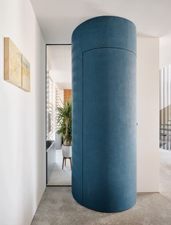 A circular coat closet helps to break up the home's linearity.