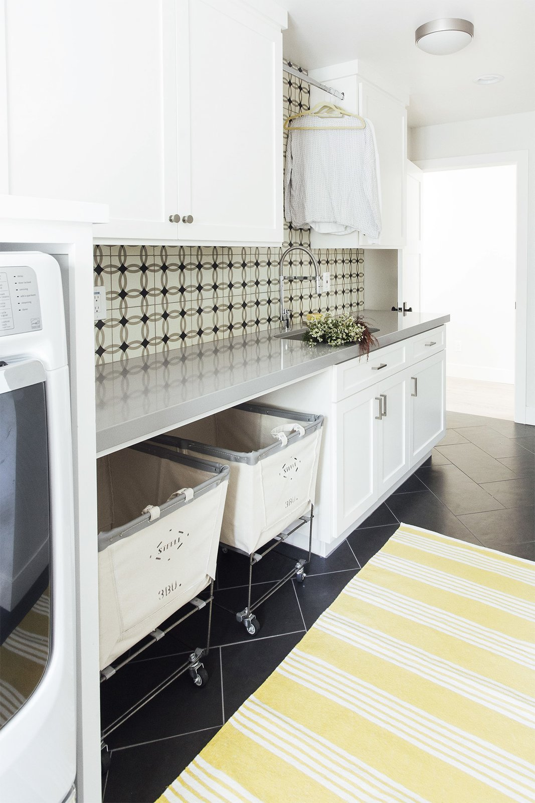 Laundry Room, Side-by-Side, Tile Counter, and White Cabinet Lisac's laundry room for a home in Aptos, California, includes a deep sink and rolling bins from Steele Canvas Basket Co. to keep up with washing for a family of six.  Photo 6 of 6 in Give Your Home a Quick Refresh With This Room-by-Room Guide