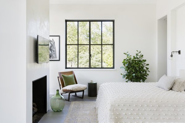 Large windows and a white bedspread lend an airy atmosphere to a California bedroom in the first home Geremia designed from the group up.