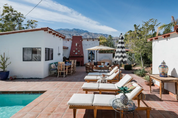 In this three-bedroom, two-and-a-half bathroom bungalow, farmhouse style meets Spanish villa. Barn doors complement the earthy red-tiled floors. Share an al fresco meal with friends and family next to the roaring outdoor fireplace, or read amongst the cacti in the shaded garden.