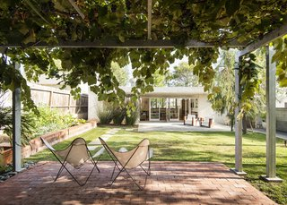 "The family's backyard features a grape arbor and a vegetable garden. ""I began gardening so our son could understand where his food comes from,"" says Onna."