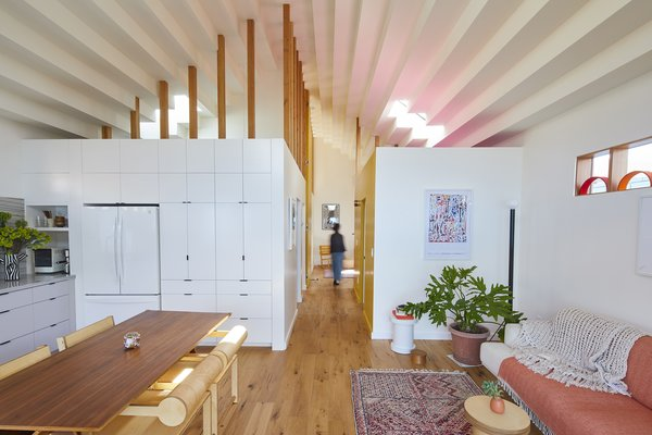 """Skylights throw pink and yellow tones across the 850-square-foot unit's stepped ceilings. """"With small spaces, we try to play with clerestory windows, skylights, and ceilings. It makes the architecture feel spacious, almost as though it's levitating."""""""