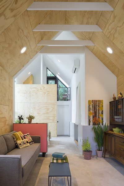 Behind a facade of stained-black cedar, plywood walls and exposed rafters lend a casual, loft-like feel to the space, while strategically placed windows and skylights bring in ample day-light.