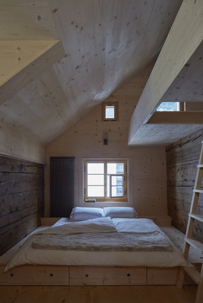 "A ladder in one of the maisonette bedrooms leads to a sleeping loft. ""Eventually the new larch will mellow, and the distinction between old and new will be harder to see,"" says Tuckey."