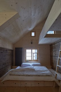 """A ladder in one of the maisonette bedrooms leads to a sleeping loft. """"Eventually the new larch will mellow, and the distinction between old and new will be harder to see,"""" says Tuckey."""