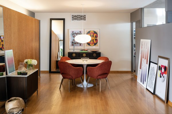 The dining room includes a vintage buffet, as well as a Florence Knoll credenza and Eero Saarinen armchairs and table. An Akari ceiling lamp by Isamu Noguchi hangs overhead. The Wire Base Low Table is by Charles & Ray Eames for Herman Miller.