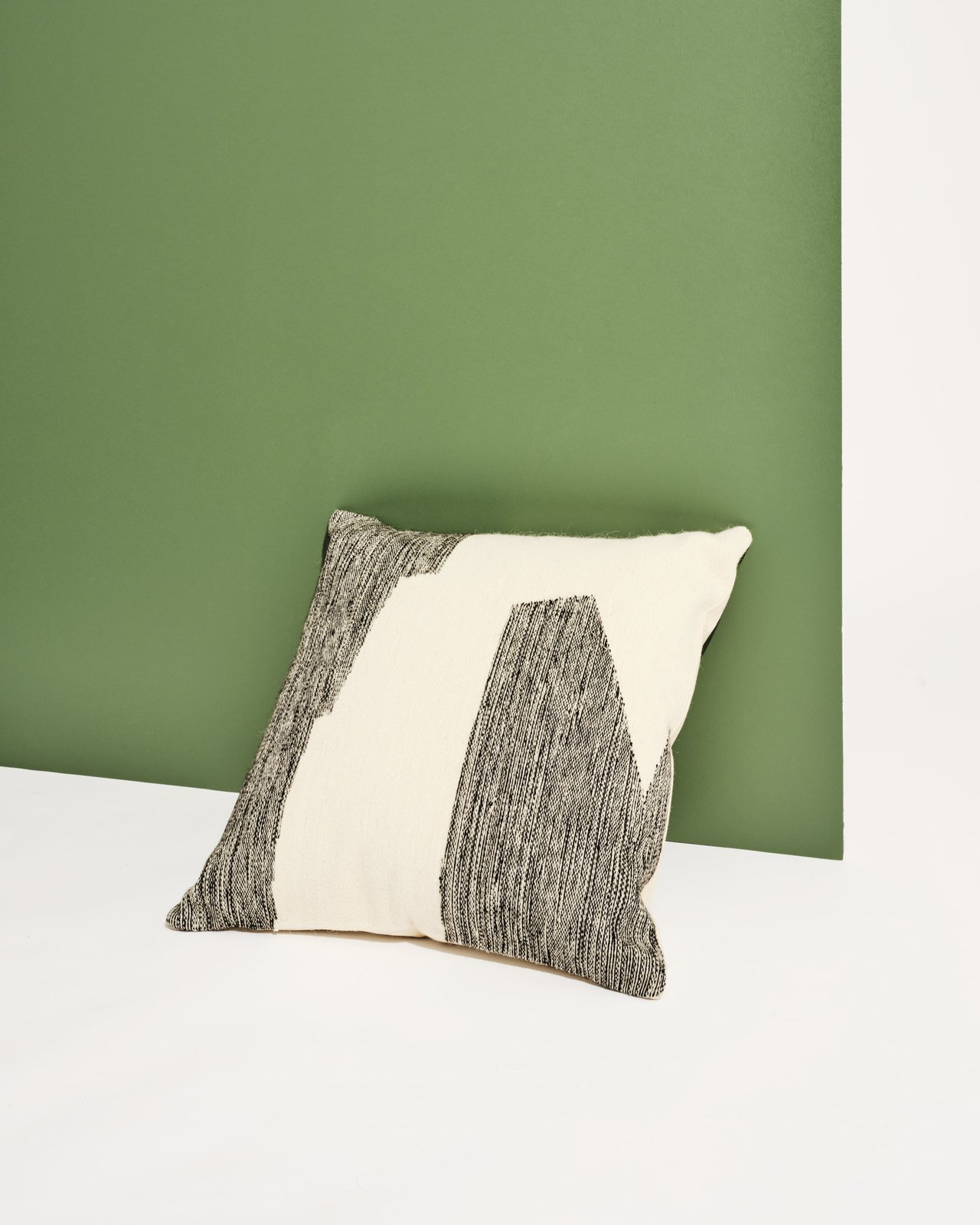 We wouldn't mind waking up next to this throw pillow from The Citizenry. Its cut-paper-inspired design is handwoven from sheep's wool in Peru.  Photo 4 of 8 in Interior Designer Lauren Geremia Shares Her Tips for a Bedroom Revamp