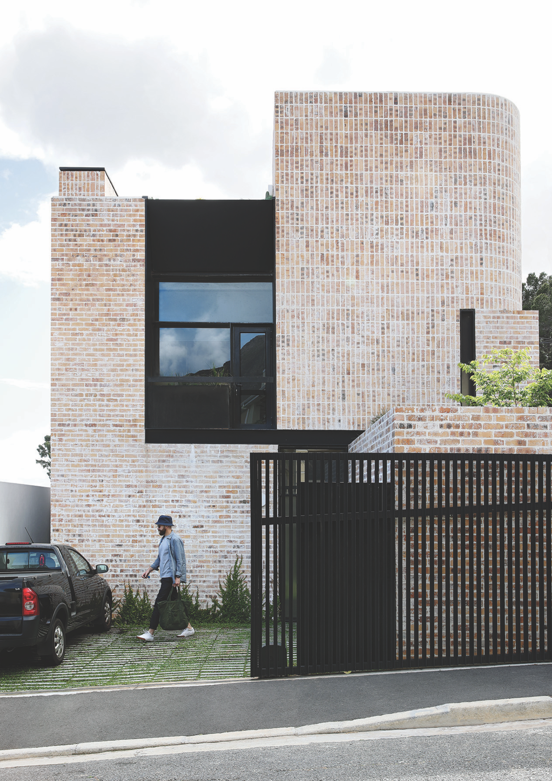 """Exterior, Flat RoofLine, Brick Siding Material, and House Building Type The Cape Town house that architect Michael Lumby designed for his friends Robyn and Clint Campbell is clad in simple, inexpensive brick in varying patterns that allow its facade to curve. The facade has a similarly rough finish. """"I wanted something that will age and patina with time and be low maintenance,"""" says Lumby.  Photo 2 of 16 in Humble Materials Get an Elevated Treatment in a '70s-Inspired Home in Cape Town"""