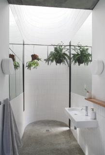 In the en suite bath on the second floor, a concrete floor gives way to a round, tiled, double-height space that culminates in a skylight. Plants hang on either side of a custom shower-head from Still Bathrooms. The faucets is from Crestial and the pendants are from Spazio Lighting.