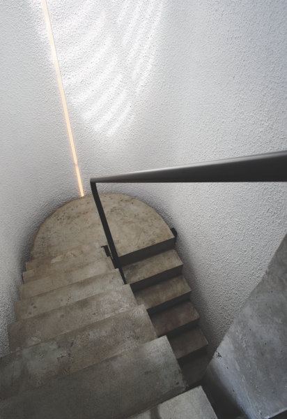 In the two-story stairwell, steps seem to float in space, thanks to a circular skylight that illuminates the walls. A continuous steel handrail connects the floors.