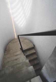在二层楼梯间,步骤似乎漂浮在空间中,由于照亮所述壁的圆形天窗。连续钢扶手连接地板。