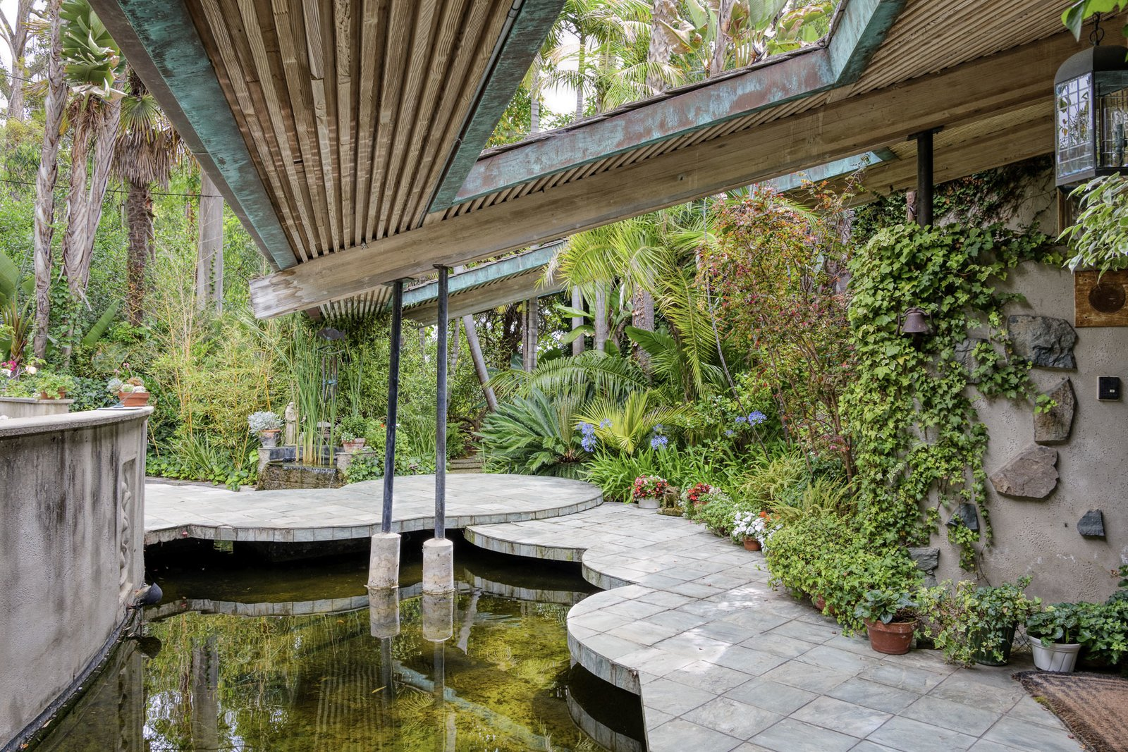 Outdoor, Trees, Back Yard, Small Pools, Tubs, Shower, and Shrubs At 19 years old, Jon P. Antelline designed the Fred Antelline House, using circular geometry to define the floor plan and landscaping. A walkway to the main entrance is framed by cutouts in the roof overhang, along with overlapping concrete slabs surrounding a water feature.  Photo 2 of 16 in A One-of-a-Kind Midcentury Modern Has Resurfaced on the Market to the Tune of $3.5M