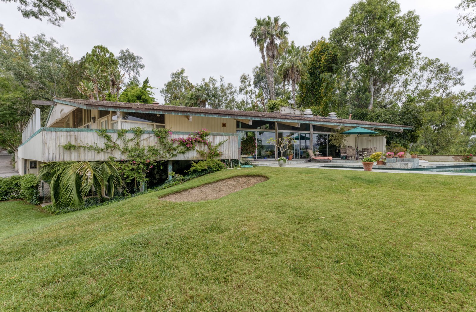 Outdoor A rear view of the home showing a basement level that emerges from a slope in the yard. The lower level holds one of the bedrooms and a bathroom, as well as a versatile studio space.  Photo 15 of 16 in A One-of-a-Kind Midcentury Modern Has Resurfaced on the Market to the Tune of $3.5M