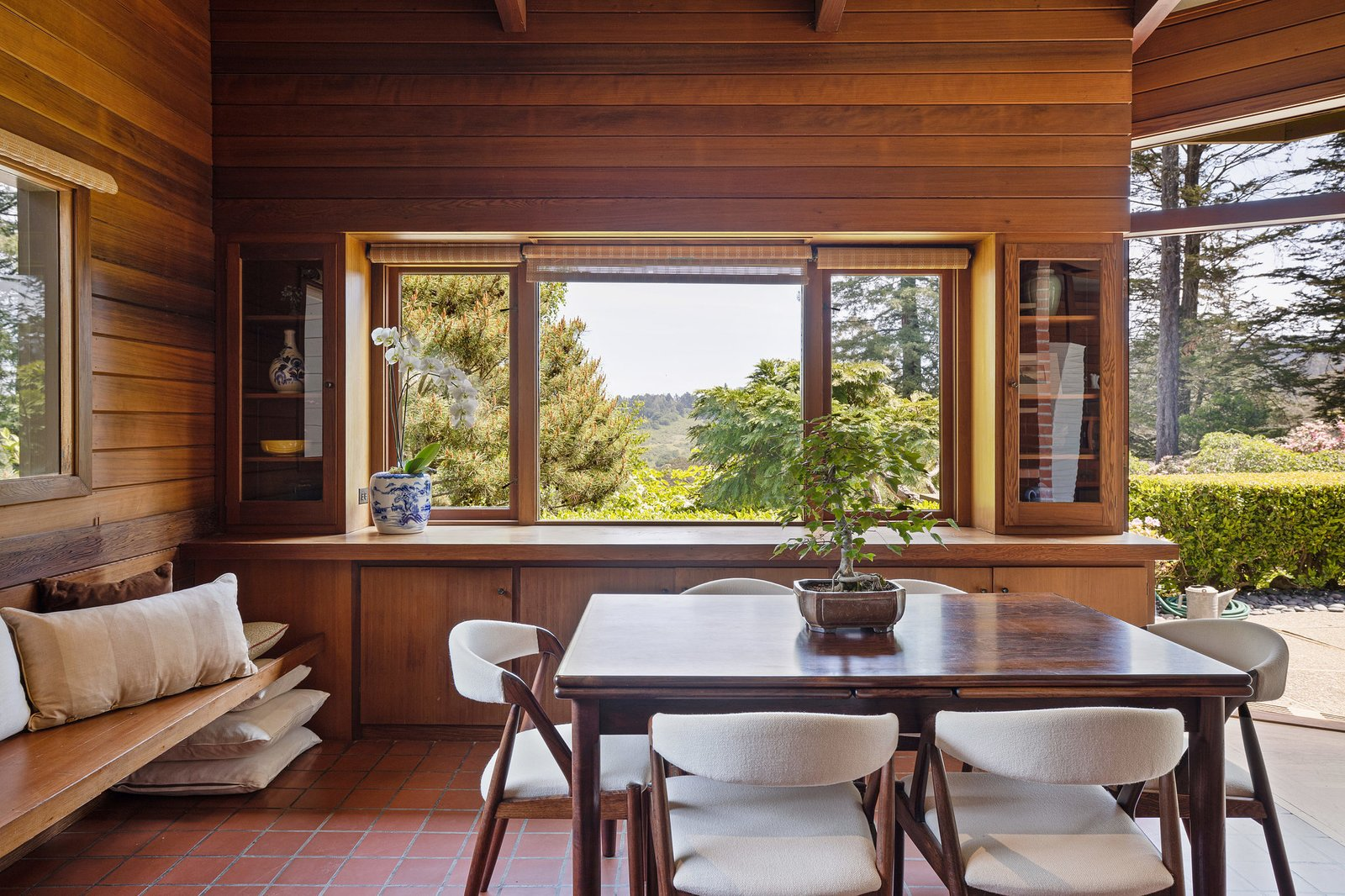 A wooden bench spans one wall in the dining room, while an expansive picture window frames views of the surrounding parkland.  Photo 8 of 21 in An Impeccable Midcentury Compound in the Berkeley Hills Wants $3.4M