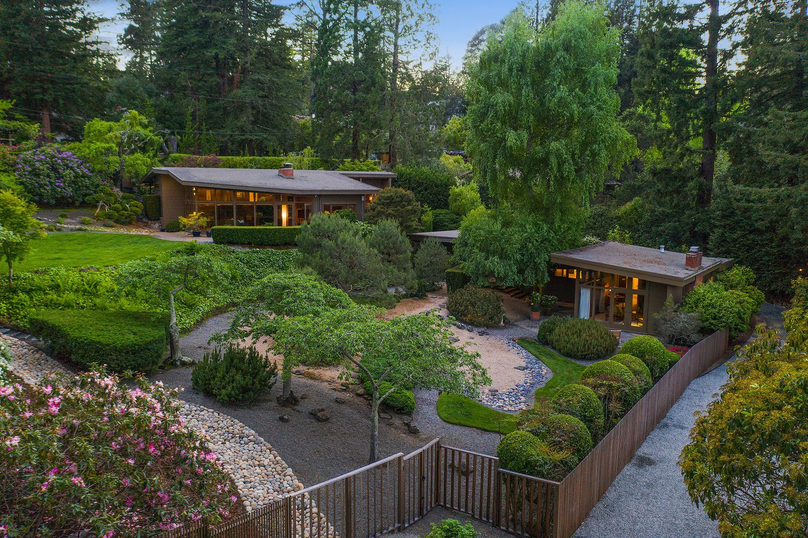 Surrounded by a verdant landscape, a restored two-property estate is nestled in the hills of Berkeley, California. A three-bedroom main residence and a one-bedroom guesthouse are joined by thoughtful landscaping.  Photo 1 of 21 in An Impeccable Midcentury Compound in the Berkeley Hills Wants $3.4M