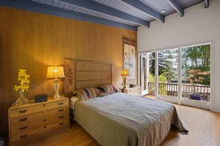 A blue-painted ceiling adds a touch of color in the master suite, which also offers a private outdoor space.