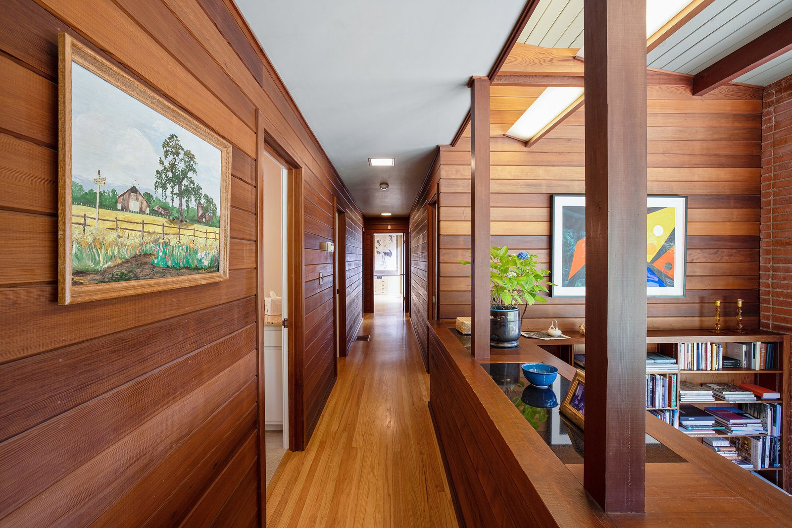 Wood lines the hallway leading to each of the home's three bedrooms.  Photo 11 of 21 in An Impeccable Midcentury Compound in the Berkeley Hills Wants $3.4M