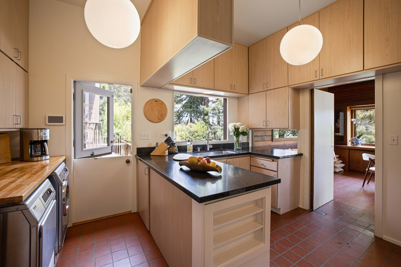 The kitchen also provides direct access to the outdoor patio.  Photo 10 of 21 in An Impeccable Midcentury Compound in the Berkeley Hills Wants $3.4M