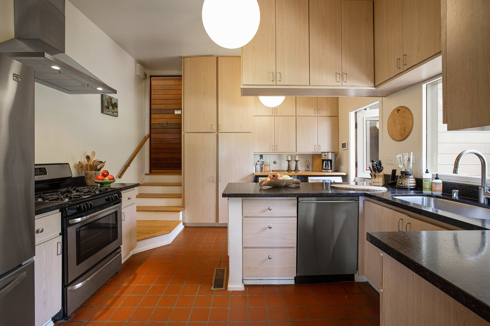 The completely remodeled kitchen boasts new appliances, cabinetry, and finishes. Natural wood cabinets contrast with the original flooring.  Photo 9 of 21 in An Impeccable Midcentury Compound in the Berkeley Hills Wants $3.4M