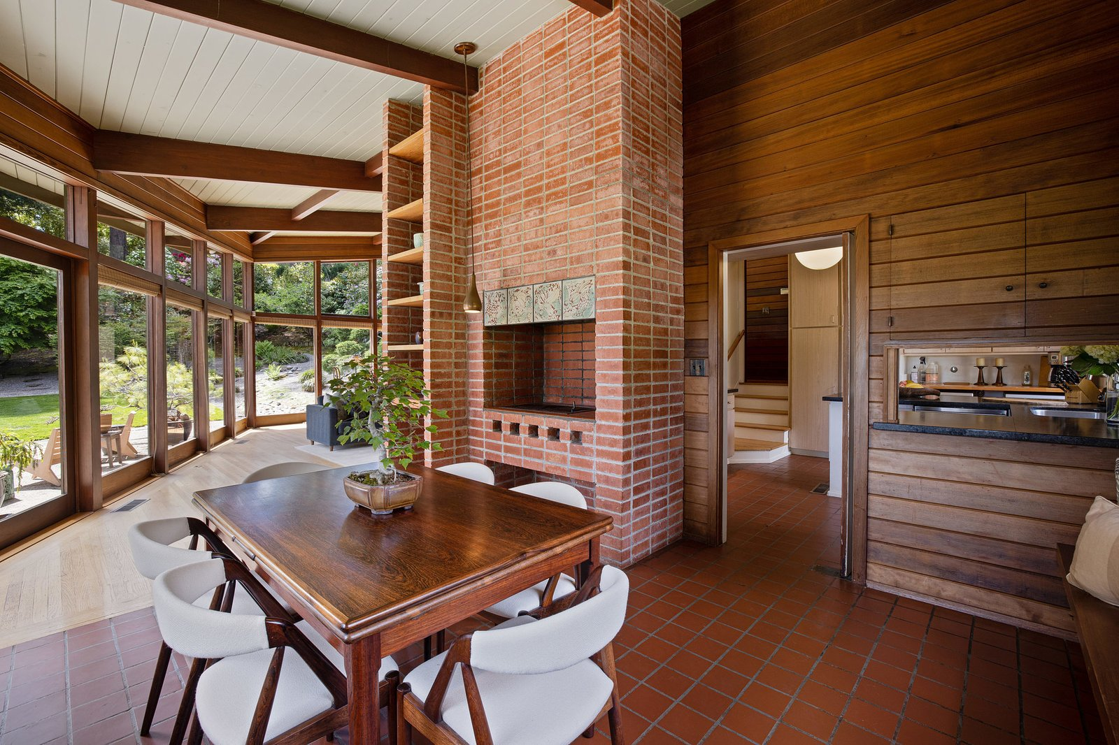 Around the bend from the living room, a dining area comes complete with an original built-in pizza oven, as well as built-in seating and storage. A small pass-through connects with the kitchen.  Photo 6 of 21 in An Impeccable Midcentury Compound in the Berkeley Hills Wants $3.4M