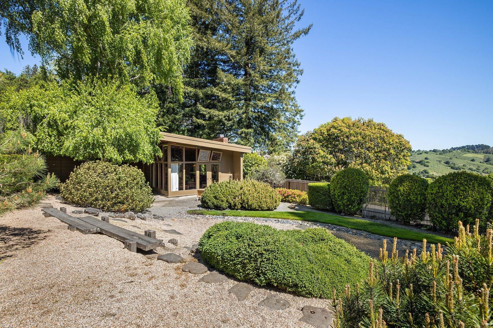 A closer look at the exterior of the guest house, featuring a striking backdrop of Tilden Park.  Photo 21 of 21 in An Impeccable Midcentury Compound in the Berkeley Hills Wants $3.4M